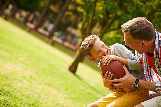 Boy playing football with father figure